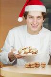 Il confettiere in cappello di Santa tiene la zolla con i biscotti immagini stock