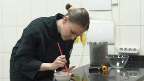 Il confettiere cucina una miscela di pasta nel ristorante per un dessert archivi video