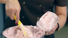 Il confettiere mette la crema nella borsa della pasticceria per decorare il dolce video d archivio