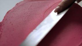 Il confettiere mette la crema rosa con la spatola della pasticceria sul dolce video d archivio