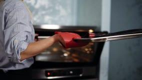 Il confettiere nella cucina prepara le preparazioni per il dessert Una ragazza nelle tirate blu di una camicia aspetta i tortini  archivi video