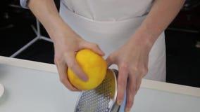 Il confettiere taglia la scorza d'arancia, grata dello zester dell'agrume che sbuccia la scorza d'arancia video d archivio