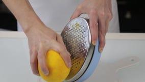 Il confettiere taglia la scorza d'arancia, grata dello zester dell'agrume che sbuccia la scorza d'arancia stock footage