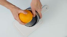 Il confettiere taglia la scorza d'arancia, grata dello zester dell'agrume che sbuccia la scorza d'arancia vista superiore 4k stock footage