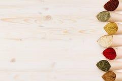 Il confine decorativo di varia polvere aromatizza il primo piano negli angoli di carta sul bordo di legno bianco con lo spazio de Fotografia Stock Libera da Diritti