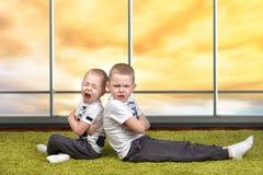 Il conflitto dei fratelli I ragazzi hanno litigato e restituito le direzioni differenti Difficoltà di relazione all'interno della fotografia stock libera da diritti