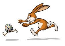 Il coniglietto di pasqua sta inseguendo un uovo di Pasqua Fotografia Stock