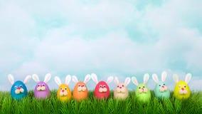 Il coniglietto di pasqua variopinto dei fronti divertenti eggs in una fila sul landcape dell'erba per le insegne sociali di media Immagine Stock