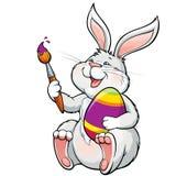 Il coniglietto felice adorabile con la spazzola dipinge l'uovo di Pasqua Immagini Stock Libere da Diritti
