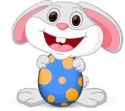 Il coniglietto sveglio di Pasqua tiene l'uovo Immagine Stock