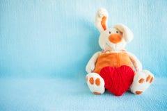 Il coniglio molle sveglio ed il rosso del giocattolo hanno tricottato il cuore su un fondo blu fotografia stock