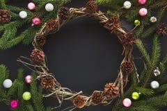 Il cono della decorazione della corona del nuovo anno o di Natale, abete si ramifica, palle di vetro variopinte su fondo nero Spa Fotografia Stock