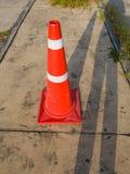 Il cono di traffico, con le bande bianche ed arancio su asfalto grigio, spazio della copia Fotografia Stock