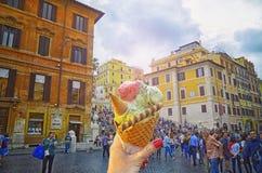 Il cono gelato italiano ha tenuto a disposizione sui precedenti della fontana famosa di Trevi fotografie stock libere da diritti