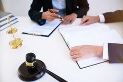 Il consigliere giuridico femminile dell'avvocato presenta al cliente una cont. firmata fotografie stock