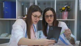 Il Consiglio di medici delle donne nell'ufficio dietro uno scrittorio Due donne l'ambulatorio considerare raggi x e discutere dop stock footage