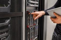 Il consulente IT Using Digital Tablet effettua un analisi guasti dei problemi con il server immagini stock libere da diritti
