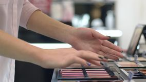 Il consumismo, donna dell'acquirente sceglie il fard per trucco del fondamento e le prove sul braccio al negozio cosmetico stock footage