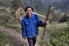 Il contadino asiatico va lavorare nei campi con la forcella della zappa Immagine Stock