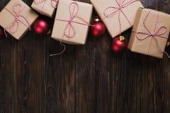 Il contenitore di regali di Natale presenta con le palle rosse su fondo di legno Fotografie Stock Libere da Diritti