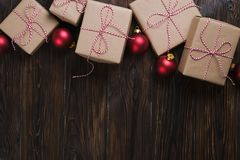 Il contenitore di regali di Natale presenta con le palle rosse su fondo di legno Immagine Stock