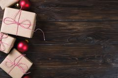 Il contenitore di regali di Natale presenta con le palle rosse su fondo di legno Fotografie Stock