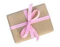 Il contenitore di regalo avvolto nel marrone ha riciclato la carta con il principale rosa vi del nastro Fotografia Stock Libera da Diritti