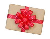 Il contenitore di regalo avvolto nel marrone ha riciclato la carta con il ribb rosso del pois Fotografia Stock