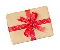 Il contenitore di regalo avvolto nel marrone ha riciclato la carta con il ribb rosso del pois Fotografie Stock Libere da Diritti