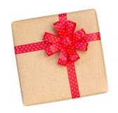 Il contenitore di regalo avvolto nel marrone ha riciclato la carta con il ribb rosso del pois Fotografia Stock Libera da Diritti
