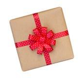 Il contenitore di regalo avvolto nel marrone ha riciclato la carta con il ribb rosso del pois Immagine Stock
