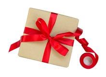 Il contenitore di regalo avvolto nel marrone ha riciclato la carta con la cima rossa dell'arco del nastro Immagine Stock Libera da Diritti