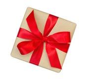 Il contenitore di regalo avvolto nel marrone ha riciclato la carta con la cima rossa dell'arco del nastro Fotografia Stock