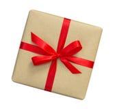 Il contenitore di regalo avvolto nel marrone ha riciclato la carta con la cima rossa dell'arco del nastro Fotografia Stock Libera da Diritti