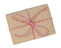 Il contenitore di regalo avvolto nel marrone ha riciclato la carta con la corda rossa e bianca Fotografia Stock Libera da Diritti