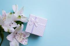Il contenitore di regalo bianco con alstroemeria fiorisce su backgroun blu-chiaro Fotografia Stock Libera da Diritti
