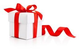 Il contenitore di regalo bianco ha legato l'arco rosso del nastro isolato su fondo bianco fotografia stock