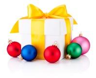 Il contenitore di regalo bianco ha legato il nastro giallo ed ha colorato le bagattelle di Natale isolate su fondo bianco fotografia stock