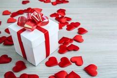 Il contenitore di regalo bianco su un fondo e su un cuore grigi del tessuto modella Fotografie Stock Libere da Diritti