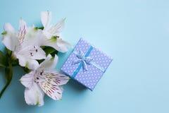 Il contenitore di regalo blu con alstroemeria fiorisce su fondo blu-chiaro Immagini Stock Libere da Diritti