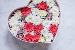 Il contenitore di regalo con cuore ha modellato i fiori su fondo di marmo grigio immagine stock libera da diritti