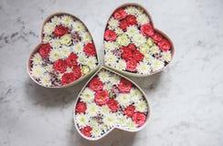 Il contenitore di regalo con cuore ha modellato i fiori su fondo di marmo grigio fotografia stock