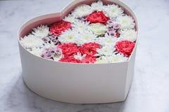 Il contenitore di regalo con cuore ha modellato i fiori su fondo di marmo grigio fotografia stock libera da diritti