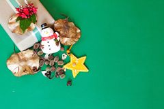 Il contenitore di regalo con il fiore rosso, il pupazzo di neve, pigne, asciuga le foglie e la decorazione della stella su fondo  Immagini Stock