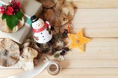 Il contenitore di regalo con il fiore rosso, il pupazzo di neve, pigne, asciuga le foglie, la decorazione della stella ed il nast Immagini Stock
