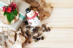 Il contenitore di regalo con il fiore rosso, il pupazzo di neve, pigne ed asciuga le foglie su fondo di legno Fotografie Stock