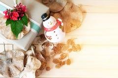 Il contenitore di regalo con il fiore rosso, il pupazzo di neve, pigne ed asciuga le foglie su fondo di legno Fotografia Stock