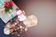 Il contenitore di regalo con il fiore rosso, il pupazzo di neve, pigne ed asciuga le foglie su fondo nero Immagini Stock Libere da Diritti