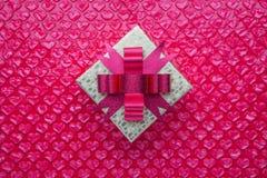 Il contenitore di regalo dell'oro con l'arco rosa ed il cuore rosa ha modellato l'involucro di bolla As Fotografia Stock Libera da Diritti