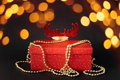 Il contenitore di regalo della decorazione di Natale con la renna nascosta dipende il bla immagine stock